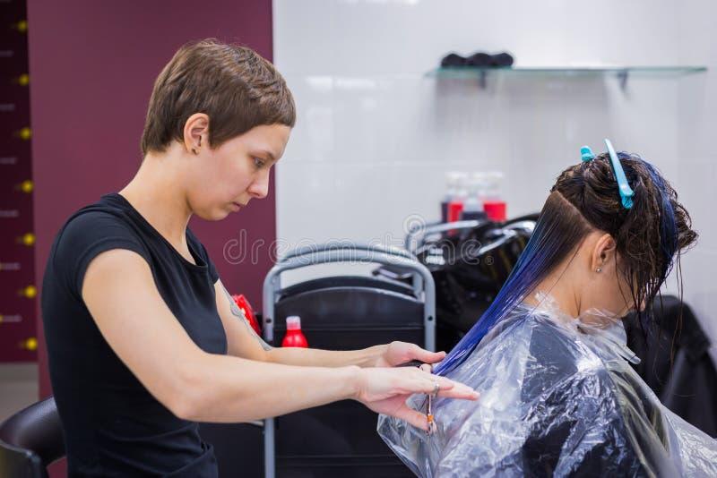 Bitande hår för frisör av kvinnaklienten arkivbilder