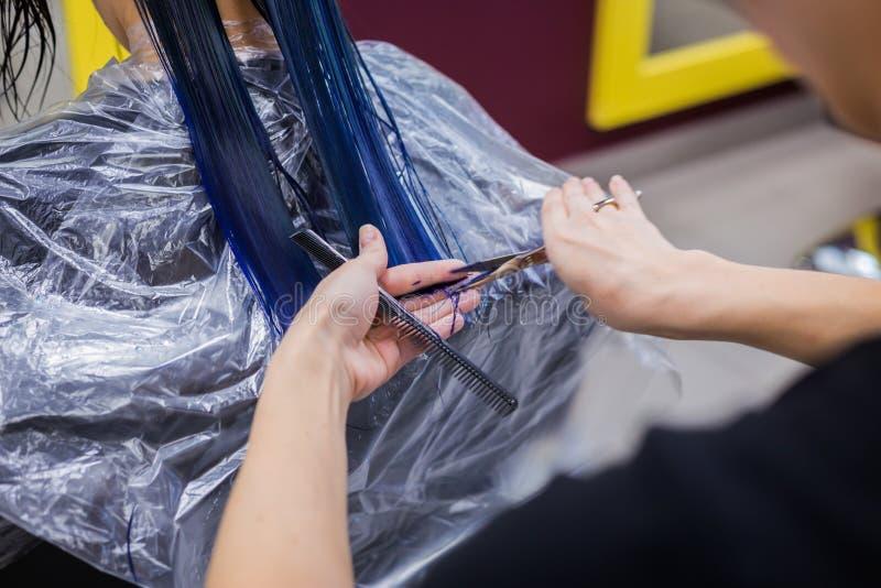 Bitande hår för frisör av kvinnaklienten arkivbild