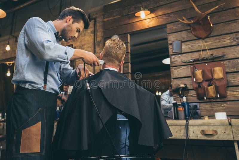 Bitande hår för manlig barberare av kunden i barberare royaltyfria foton