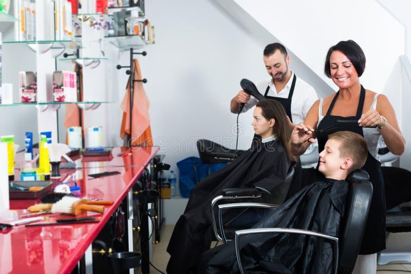 Bitande hårpojke för kvinnlig frisör i barberaresalong royaltyfri bild