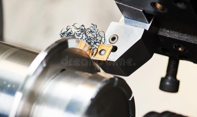 Bitande hjälpmedel på mekaniskt roterande metallarbete arkivbild