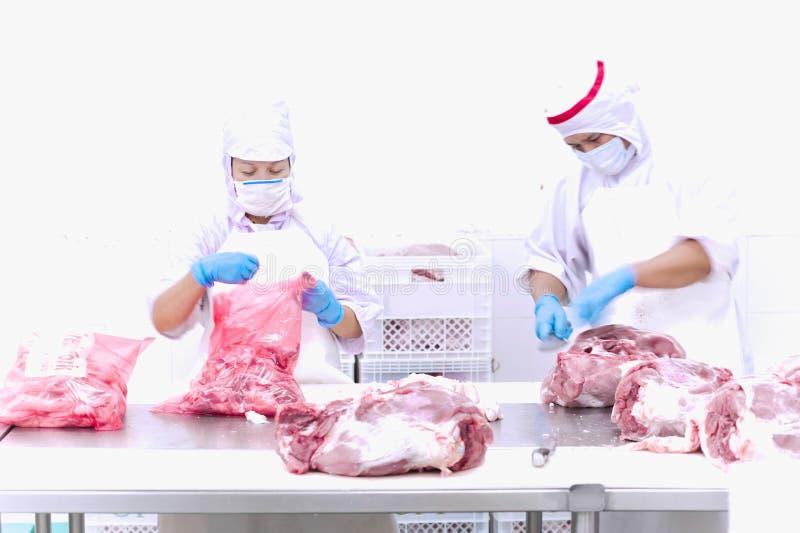 Bitande kött för slaktare på tabellen royaltyfri foto