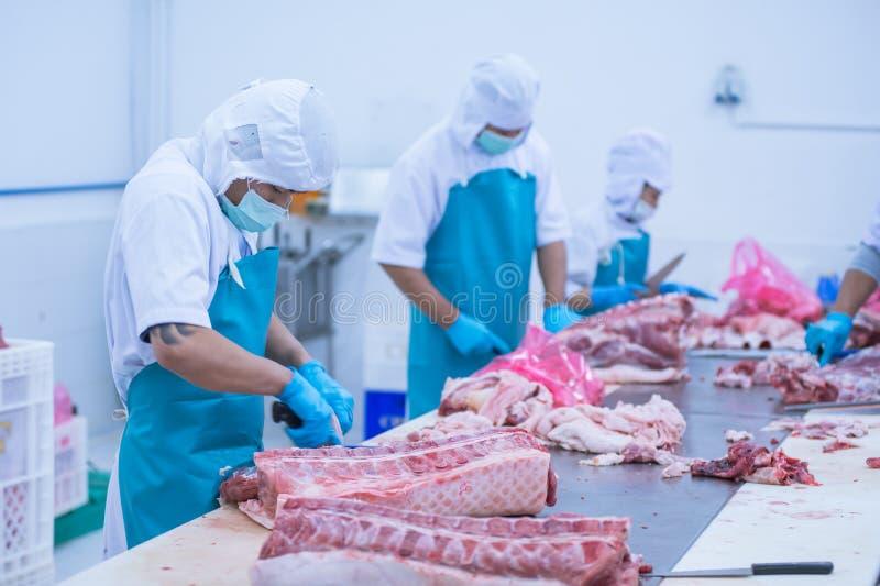 Bitande köttslakthusarbetare i fabriken arkivbilder
