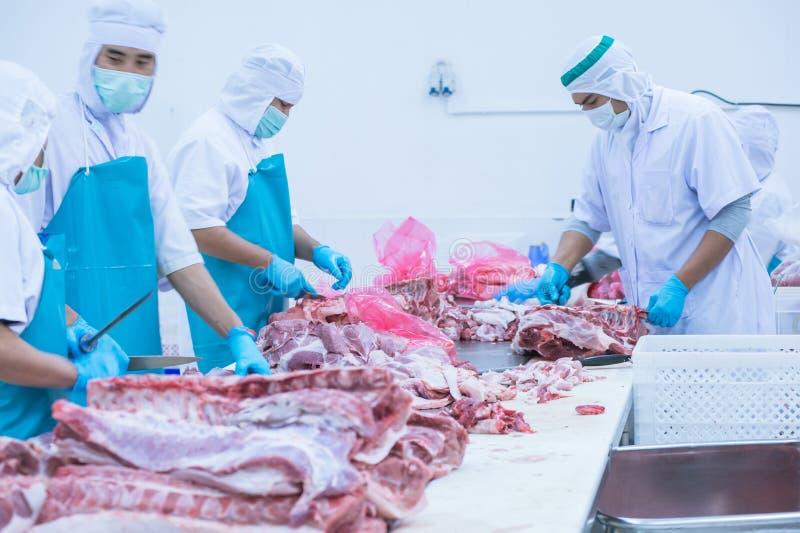 Bitande köttslakthusarbetare i fabriken royaltyfria foton