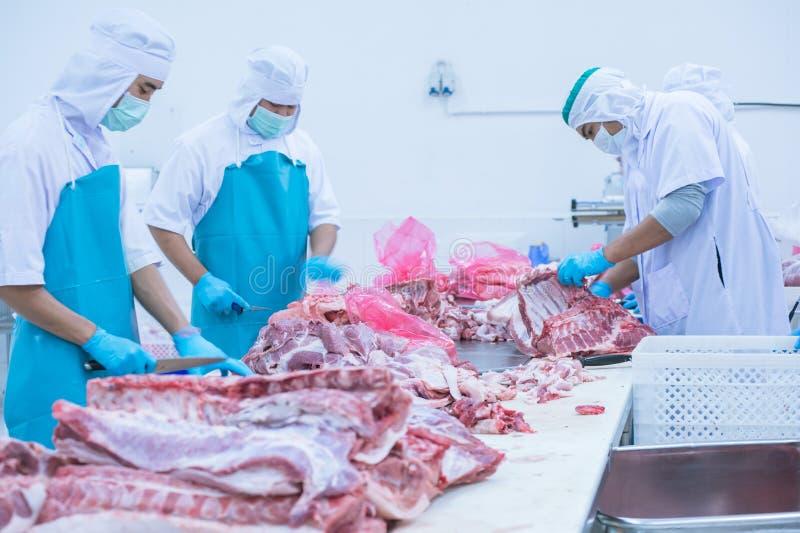 Bitande köttslakthusarbetare i fabriken royaltyfri bild