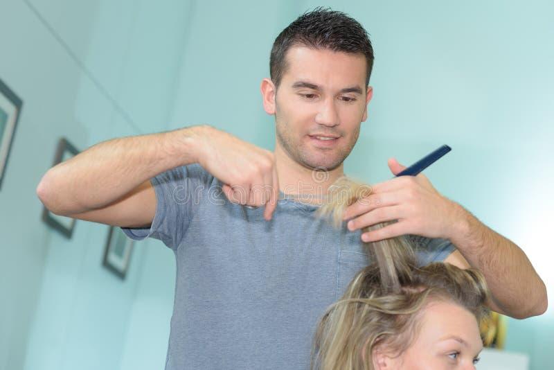 Bitande kundhår för lycklig ung manlig frisör på salongen arkivfoton