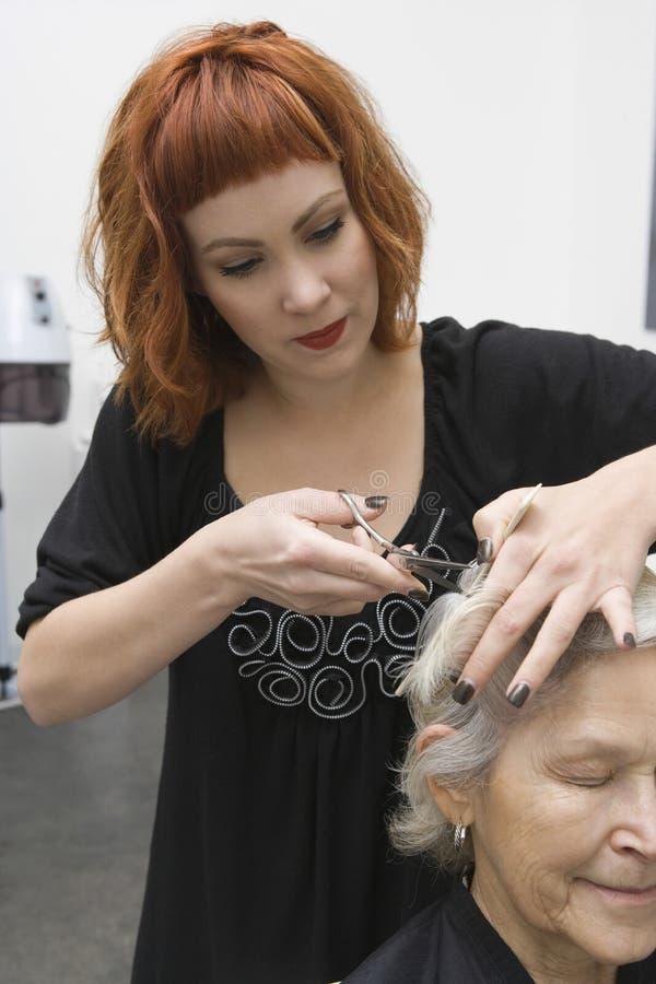 Bitande kvinnliga klients för kvinna hår i salong royaltyfri fotografi