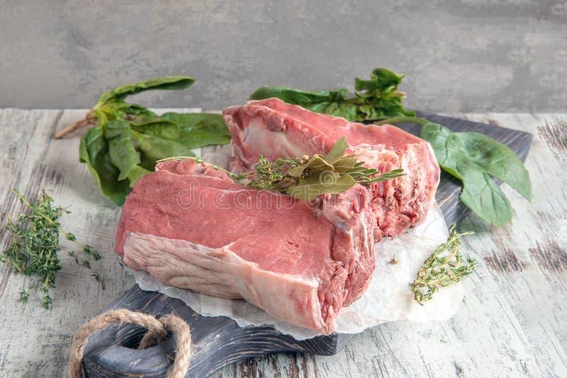 Bitande nötkött för att grilla på en träskärbräda med spenat, rosmarin och Provencal örter för marinad kopiera avstånd royaltyfri fotografi