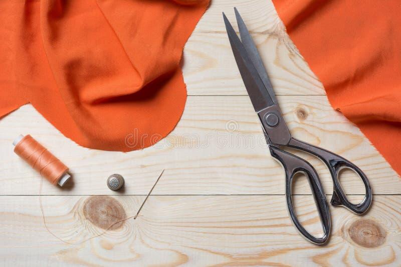 Bitande orange tyg med en taylor scissors på trätabellen royaltyfri foto