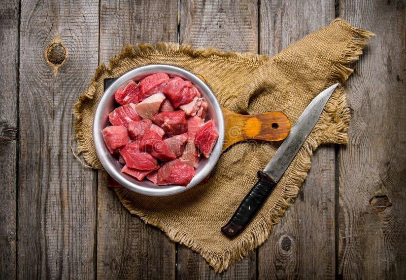 Bitande rått kött en stor kniv trägrund tabell för djupfält royaltyfria foton