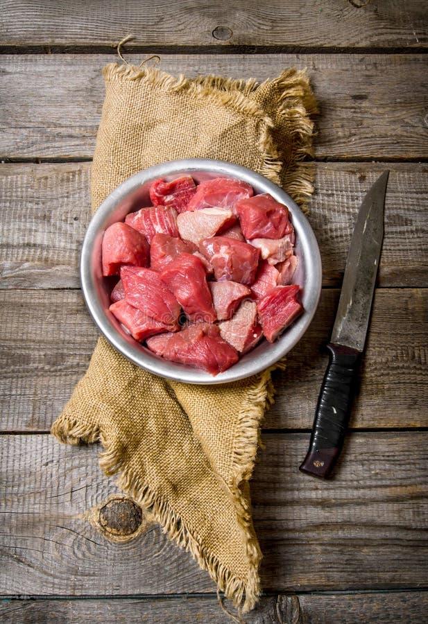 Bitande rått kött en stor kniv trägrund tabell för djupfält royaltyfria bilder
