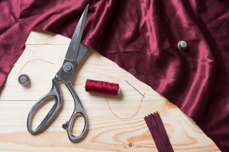 Bitande rödbrunt tyg med en taylor scissors på trätabellen arkivfoton