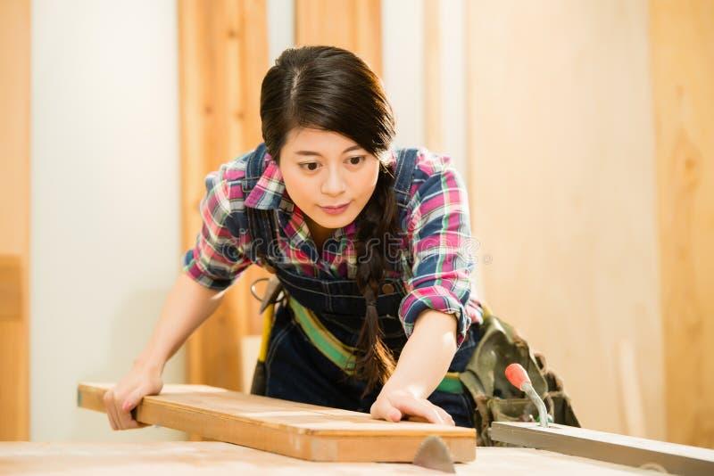 Bitande trä för ung kvinnlig snickare arkivfoton