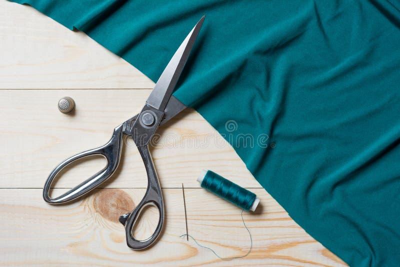 Bitande turkostyg med en taylor scissors på trätabellen royaltyfri bild