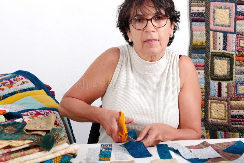Bitande tyg för mogen brunettkvinna för att sy patchworken royaltyfria foton