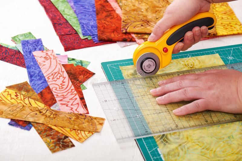 Bitande tygstycken för process vid den roterande skäraren på matt användande linjal fotografering för bildbyråer