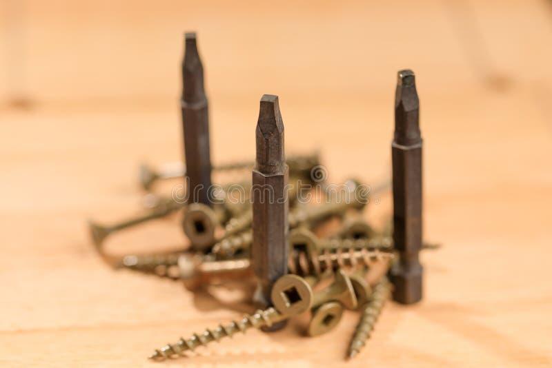 Bitar för skruvmejslar tillsammans med flera skruvar som förläggas på ett trä royaltyfri foto