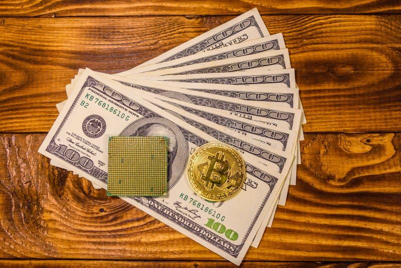 Bitcoin、微处理器和一百元钞票在木桌上 顶视图 库存图片