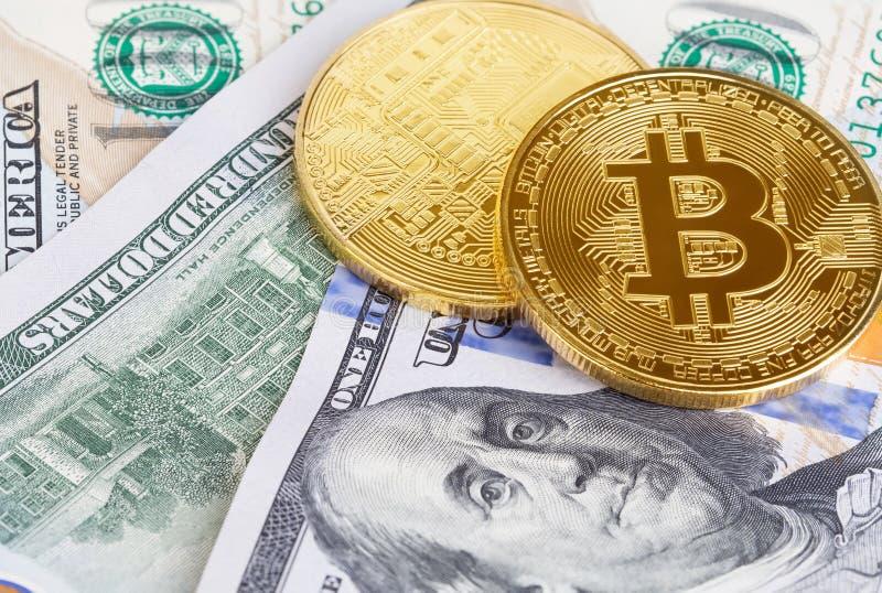 bitcoin两枚硬币在一百美元钞票的  交换一美元的bitcoin现金 免版税库存照片