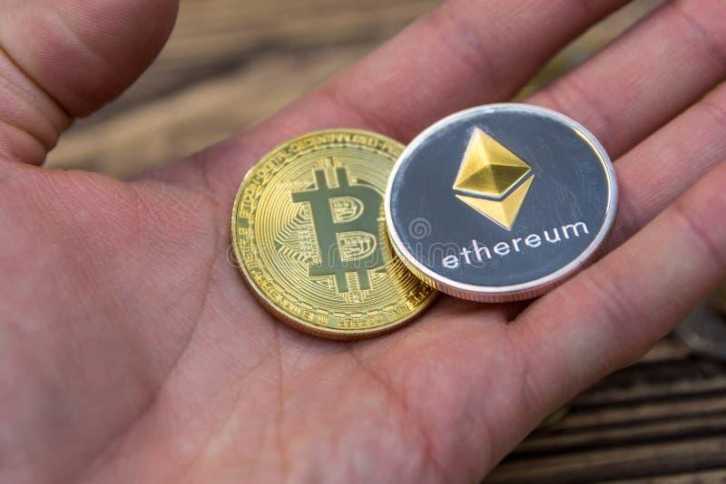 Bitcoin和ethereum说谎供以人员手特写镜头 免版税图库摄影