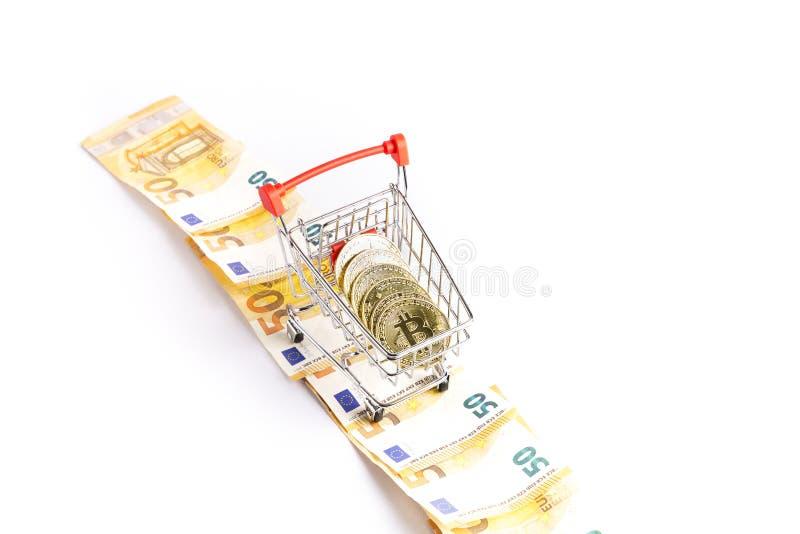 Bitcoin在购物车的金币在一些张欧洲票据 免版税库存图片