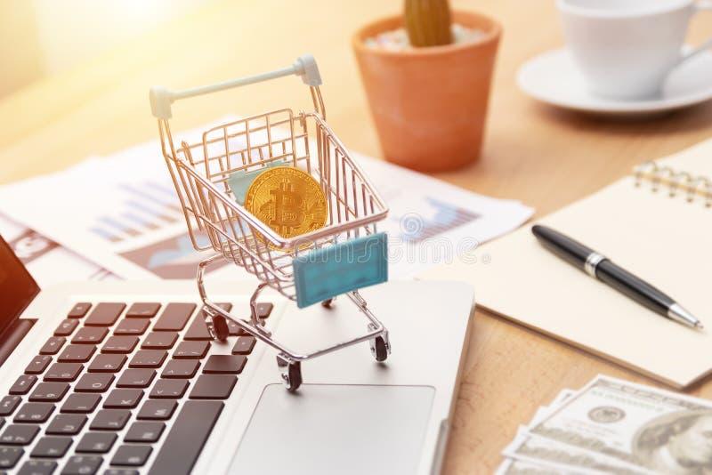Bitcoin汇兑投资通过网上商业概念 在推车的金黄bitcoin在手提电脑键盘在工作区的 库存图片
