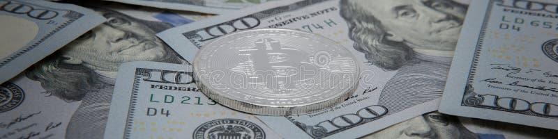 bitcoin的硬币以美元笔记为背景的 bitcoin最普遍的cryptocurrency在世界上 免版税库存照片
