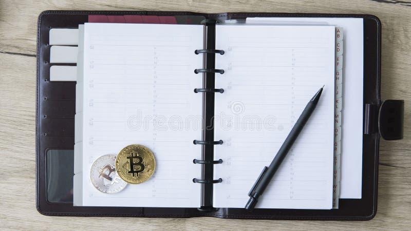 Bitcoin矿工笔记本  金子和在一个开放笔记本的银Bitcoin和笔 自由空间为在投入了文本页 免版税库存照片