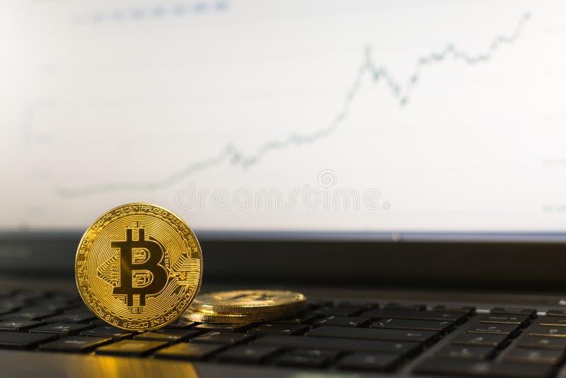 Bitcoin站立在有上升的图的膝上型计算机键盘的cryptocurrency硬币在背景 库存照片