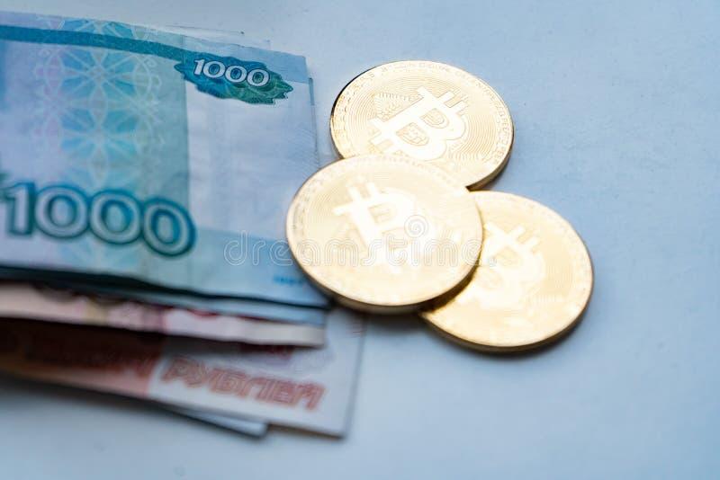Bitcoin金子和俄罗斯卢布 在俄罗斯卢布背景的Bitcoin硬币  库存照片