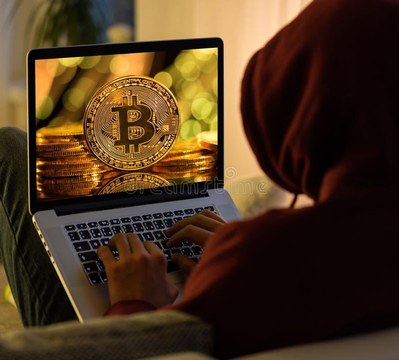 Bitcoin金币和匿名黑客sittign与膝上型计算机 库存图片