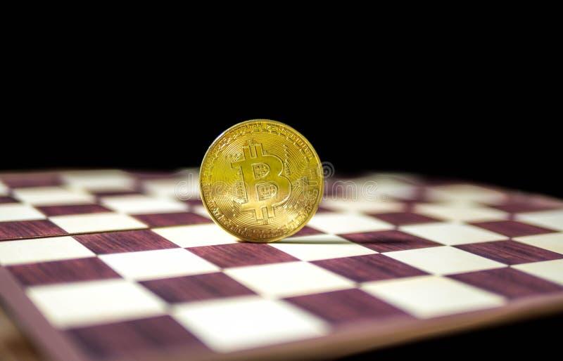 Bitcoin,在黑背景隔绝的棋盘的金黄硬币 图库摄影