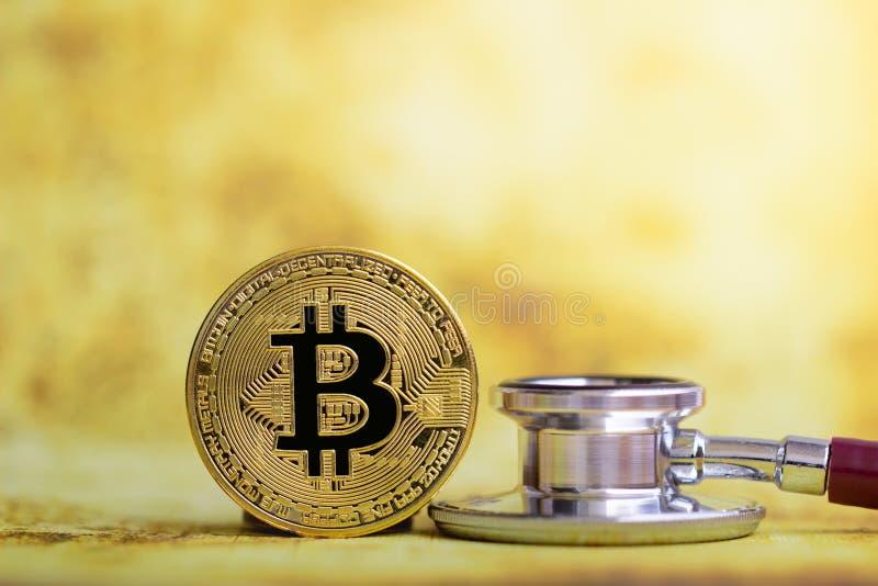 Bitcoin золота с проверкой стетоскопа вверх на белом здравоохранении предпосылки стоковая фотография rf