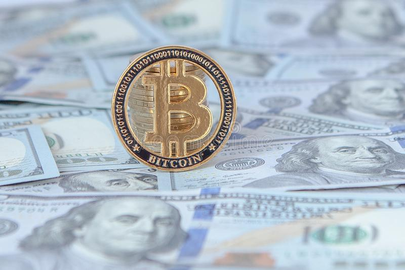 Bitcoin against the background of dollar bills. exchange bitcoin for dollars. fall of bitcoin royalty free stock photo