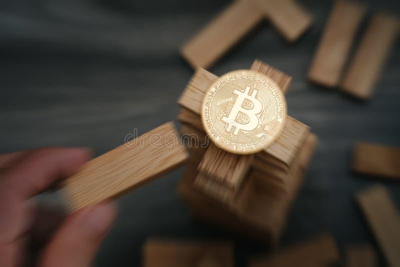 Bitcoin auf den hölzernen Bausteinen ragen mit der Hand hoch, die ein b bewegt stockbild