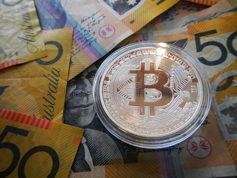 Bitcoin on Australian dollar. Silver cryptocurrency Bitcoin on Australian $50 dollar notes stock photo