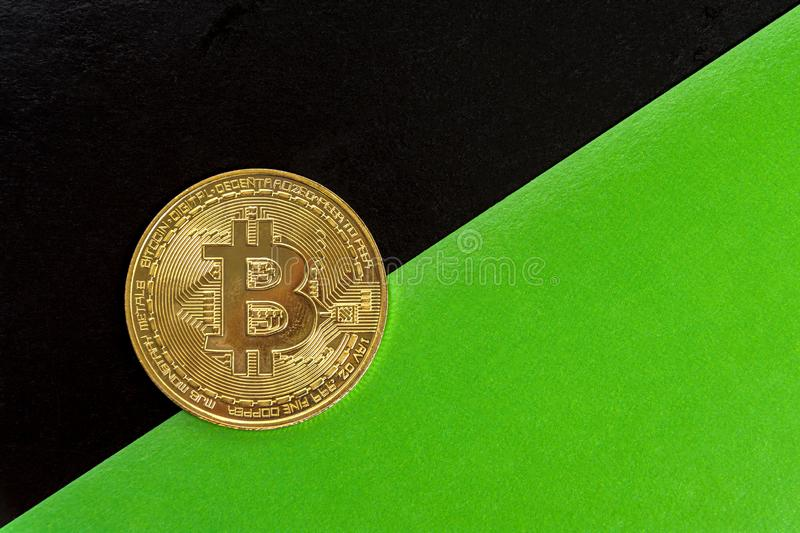 Bitcoin on the background of black and green sheets of paper laid diagonally. The concept of rising value and appreciation of stock images