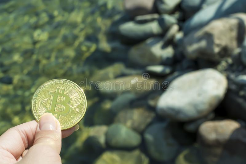 Bitcoin on the background of stones in the ocean. Financial success, growth, wealth. Bitcoin on the background of stones in the stock images