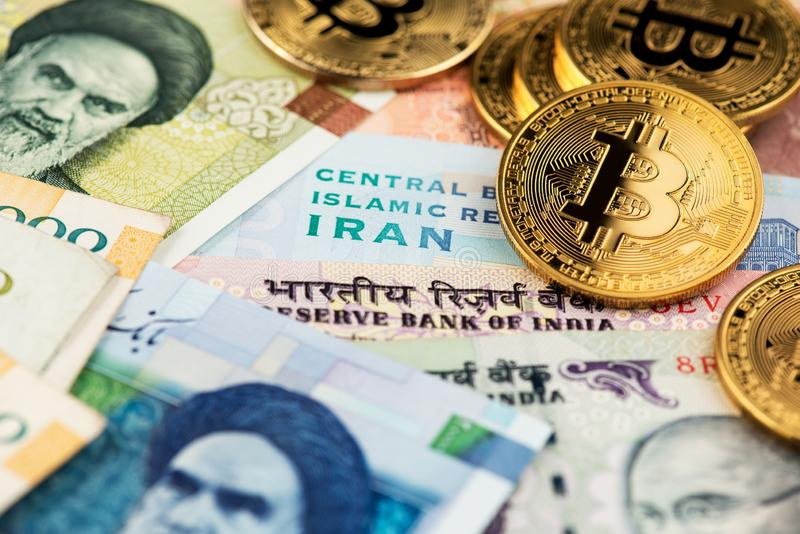 Bitcoin BTC cryptocurrency coins on Iranian and Indian currency banknotes close up image. Cryptocurrency Bitcoin BTC with Iranian Rial and Indian Rupee money royalty free stock images