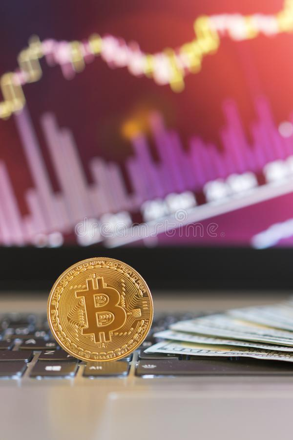 Bitcoin, chart and us dollar. Finance trading. Dollar bills laying on a laptop with bitcoin charts on a blurred background. Vertical photo stock photography