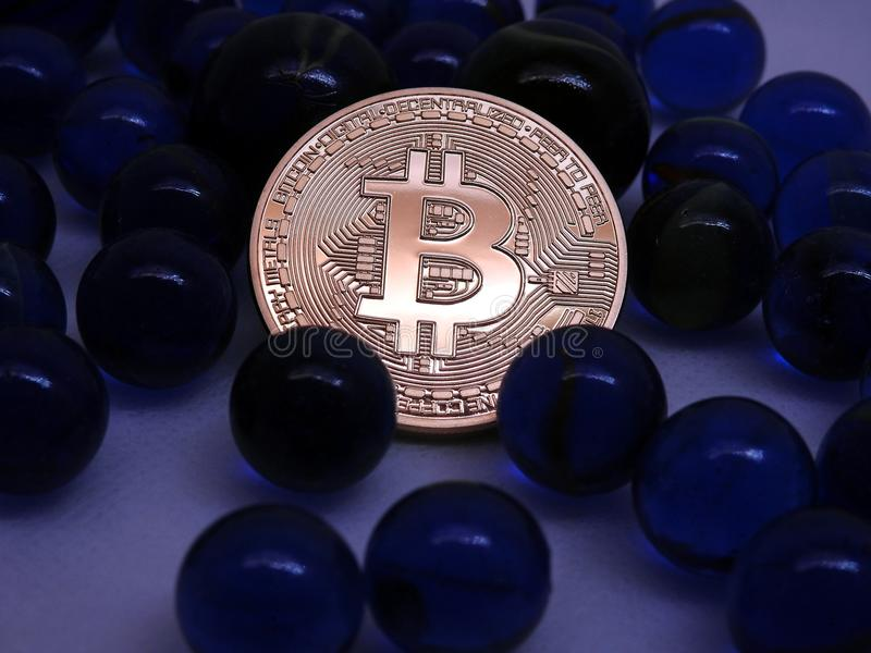 Bitcoin coin between blue glass marbles royalty free stock photos