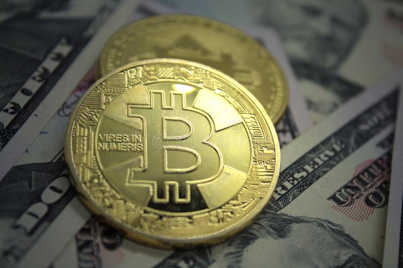 Bitcoin BTC Golden Cryptocurrency Coin Lying on a Money Background. Bitcoin Coin on a Dollars. Golden metal bitcoin on dollar bills background. Exchange bitcoin royalty free stock photo