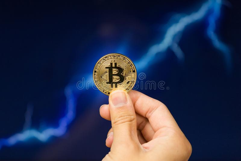 Bitcoin coin in front of lightning. Man holding Bitcoin gold coin in front of lightning network concept background royalty free stock images
