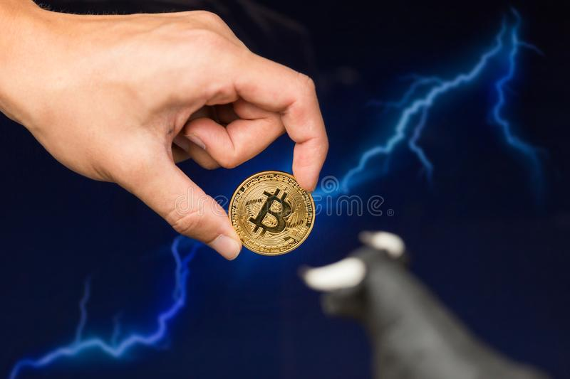 Bitcoin coin in front of lightning. Man holding Bitcoin gold coin in front of lightning network concept background royalty free stock photography