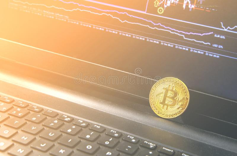 Bitcoin coin placed on modern black notebook . Close-Up photo Bitcoin. Exchange virtual value, crypto digital money . Background Live Stock trading through stock photo
