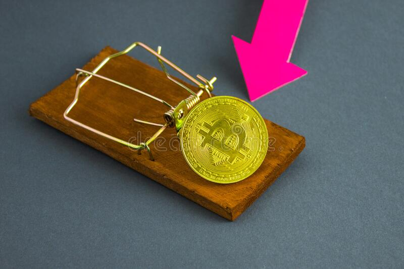 Bitcoin coin in a wooden mousetrap and a red arrow royalty free stock image
