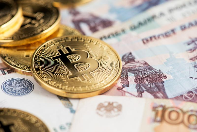 A close up image of bitcoins with Russian rubles banknotes. stock images