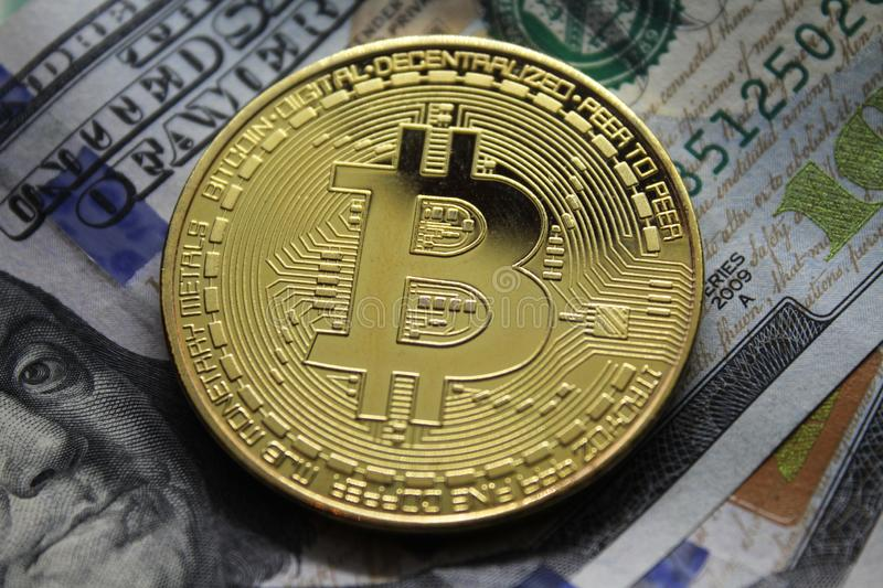 Bitcoin BTC Golden Cryptocurrency Coin Lying on a Dollar Money Background.Electronic money exchange concept. Bitcoin.Crypto currency Bitcoin, BTC, Bit Coin.Macro stock photo