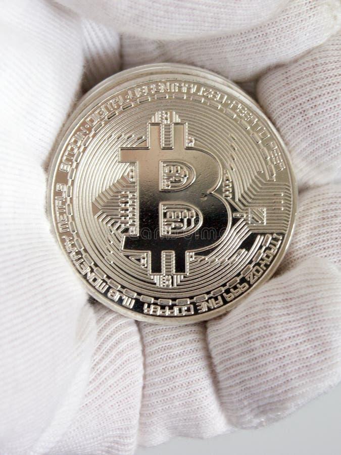 Bitcoin Crypto de la moneda a mano en el guante blanco foto de archivo