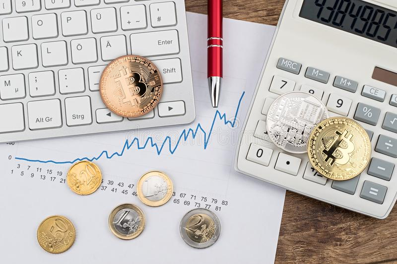 Bitcoin crypto euro currency exchange financial concept. Golden silver copper coins on calculator wooden desk with keyboard and red pencil stock photo